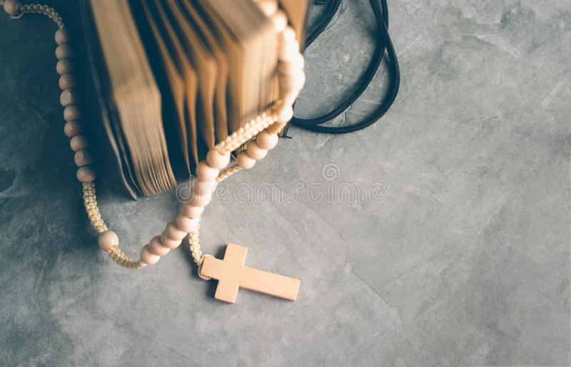 Catholic rosary beads with old book on cement table prayer, rosa. Ry background concept in vintage tone stock image
