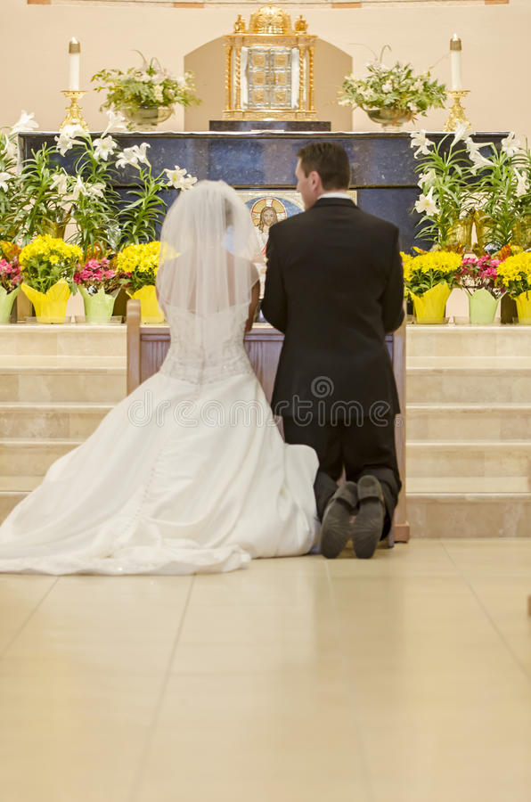 Catholic wedding. Bride and groom kneeling at the alter of a church during wedding ceremony stock images