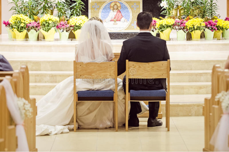 Catholic wedding. Bride and groom sitting at the alter of a church during wedding ceremony stock photography