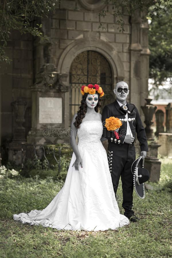 Catrin and Catrina in cemetery. With wedding dresses in an old cemetery of Guadalajara, Mexico stock image