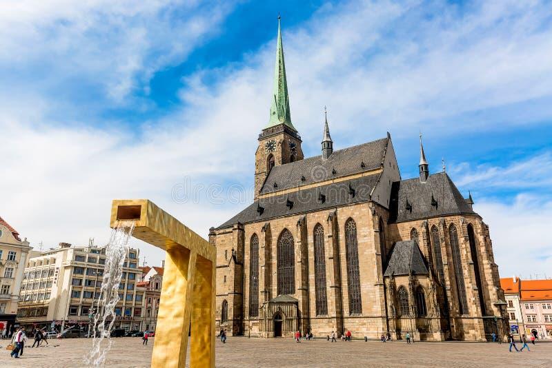 Cattedrale del ` s di St Bartholomew nel quadrato principale di Plzen con una fontana sulla priorità alta contro il giorno solegg immagine stock