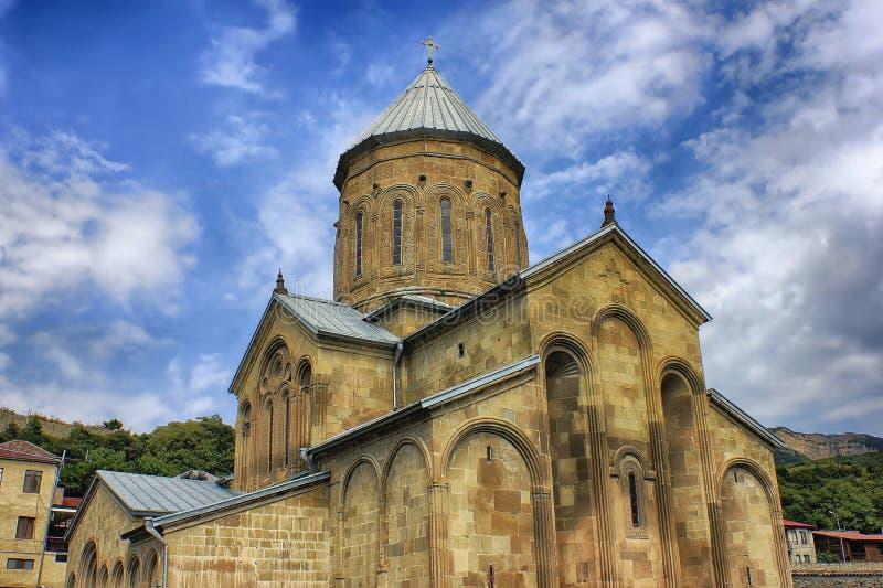Cattedrale georgiana antica sul fondo delle nuvole e delle montagne fotografia stock libera da diritti