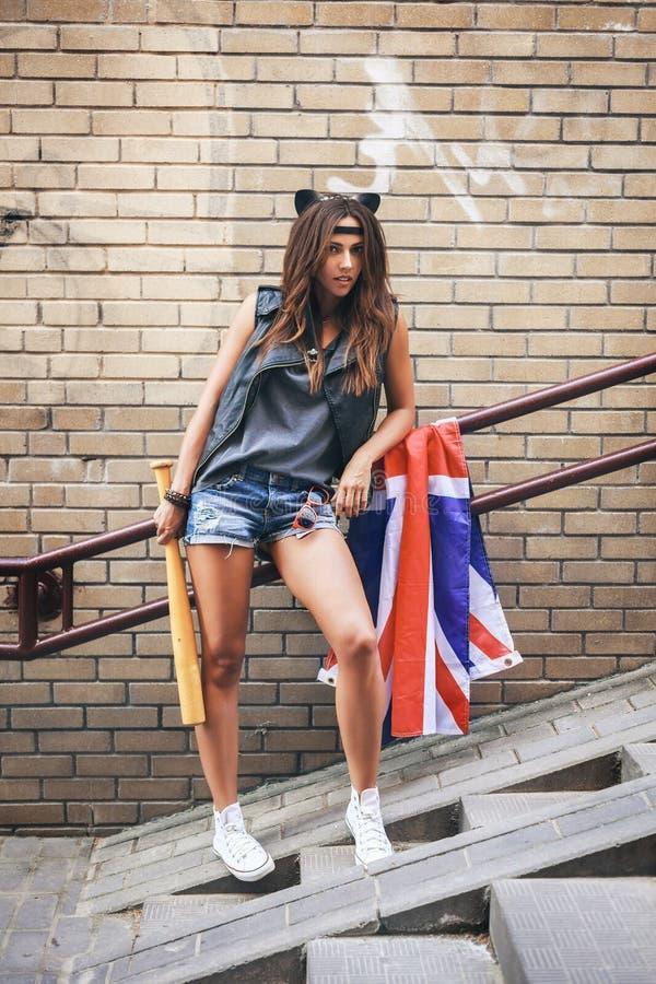 Cattiva ragazza che tiene una mazza da baseball e una bandiera di Britannici alla via fotografia stock