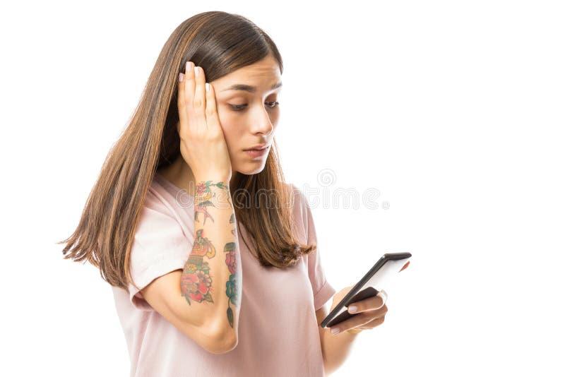 Cattive notizie turbate della lettura della donna su Smartphone fotografie stock libere da diritti
