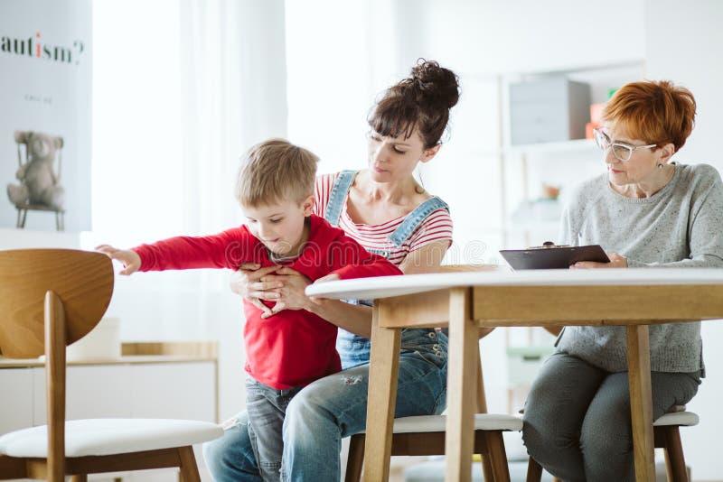 Cattivo ragazzo sveglio di comportamento che prova a funzionare durante la sessione di terapia con la suoi madre ed insegnante immagini stock libere da diritti