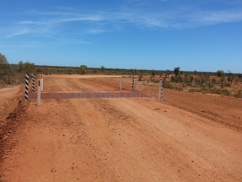 Cattle grid on gravel road in Australian Outback desert. Newly installed cattle grid on a gravel road in the Australian outback royalty free stock images