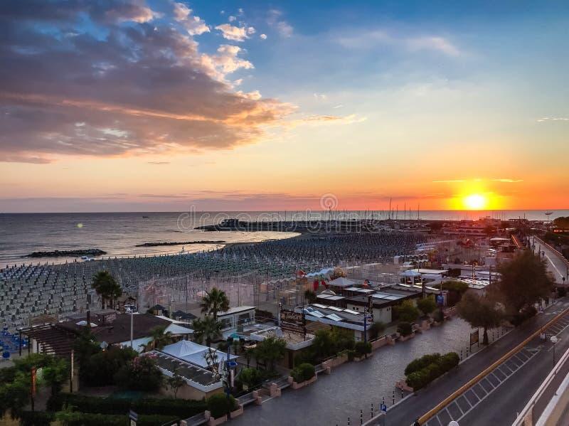 CATTOLICA, Ιταλία - ανατολή με το μπλε ουρανό πέρα από την παραλία με τον μπλε νεφελώδη ουρανό στοκ εικόνα