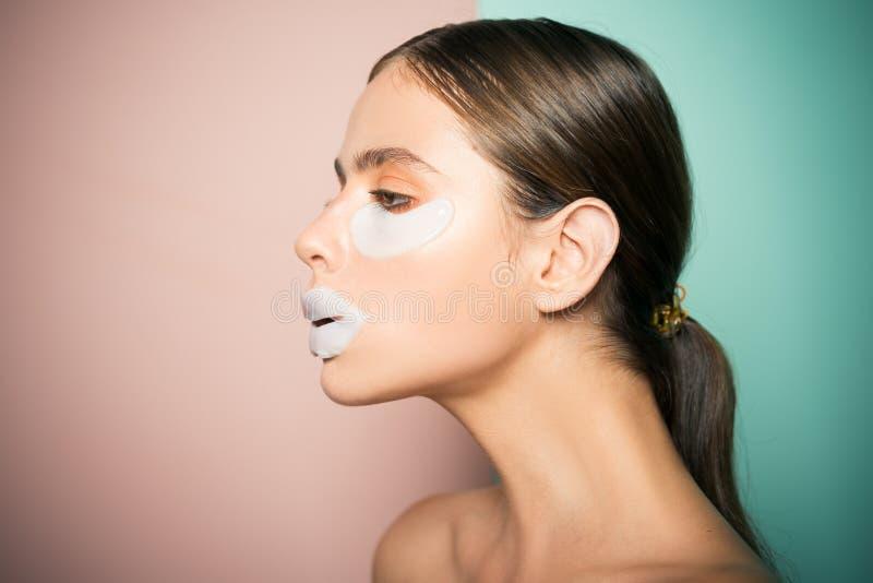 Cattura della cura della sua pelle Toppe dell'occhio di prova della ragazza Routine viziante quotidiana Cosmetici moderni Concett immagine stock