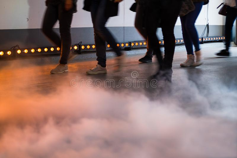 Catwalk Runway Show Event. Fashion show, catwalk runway show event - people passing lights with smoke in the foreground stock photo