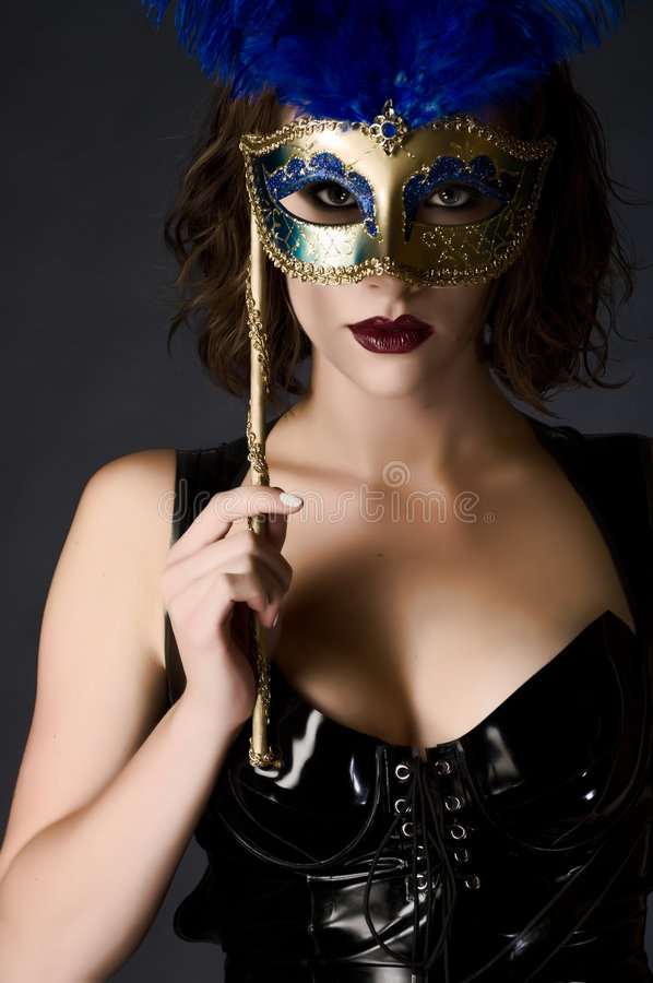 Catwoman Carnival. Beautiful young woman holding a carnival mask wearing catsuit