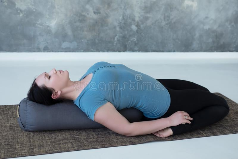 Cauacasian woman resting in reclining hero pose or Supta Virasana with bolster. Stretching after practice. Studio shot stock images