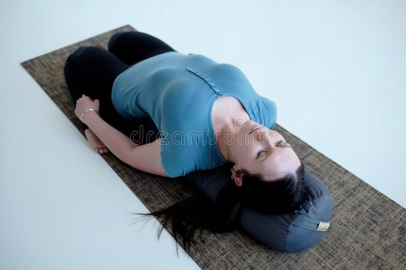 Cauacasian woman resting in reclining hero pose or Supta Virasana with bolster. Stretching after practice. Studio shot stock photography