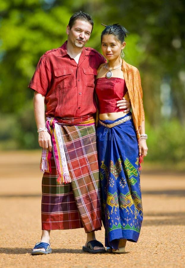 Caucásico y asiático con ropa tailandesa tradicional imagenes de archivo
