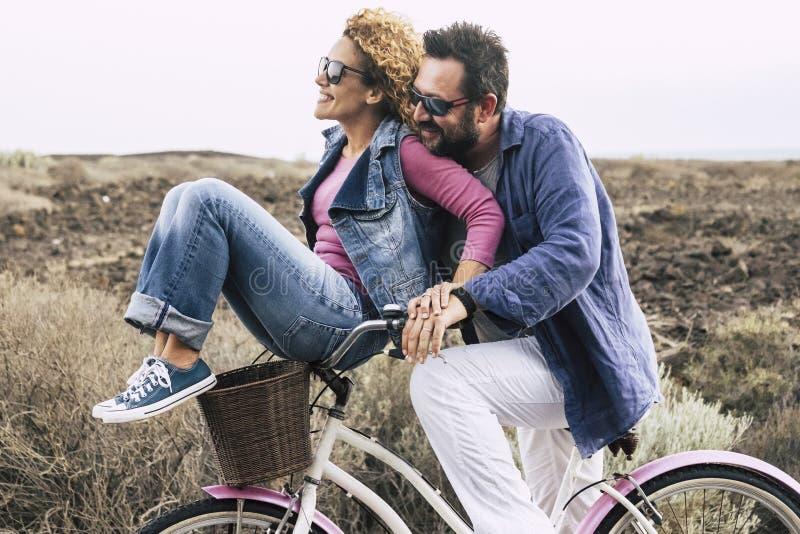Cauc?sico adulto feliz, par que se divierte con la bicicleta en pasatiempo al aire libre concepto de gente juguetona activa con l imágenes de archivo libres de regalías