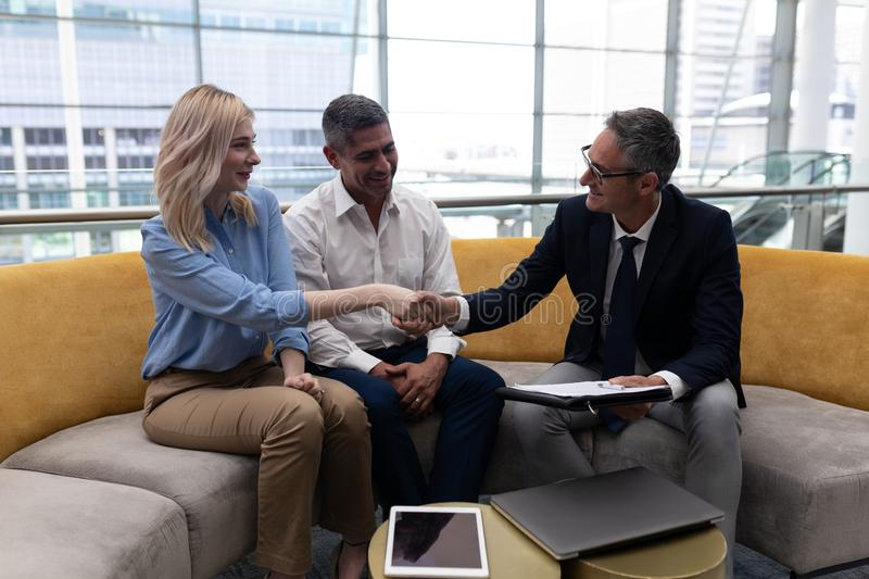 Caucaisans business executives shaking hand while sitting on the sofa stock image