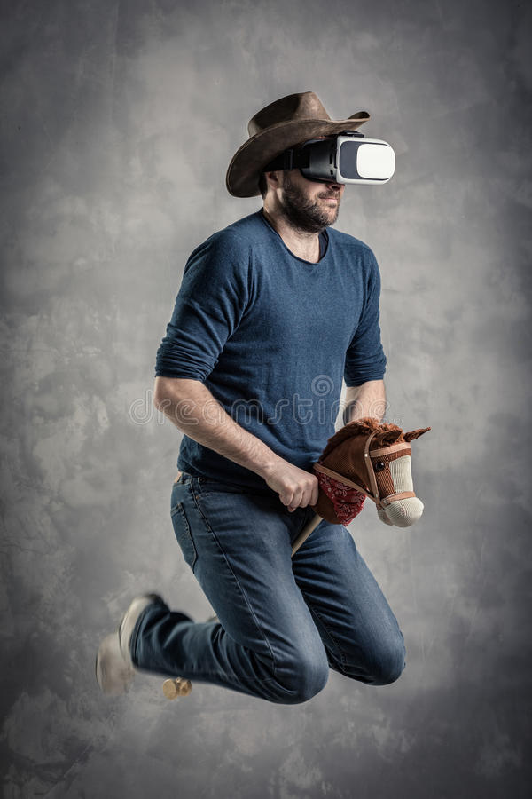 Caucasian adult man enjoy experiencing immersive Virtual Reality cowboy game simulation.VR portrait concept with western royalty free stock photo