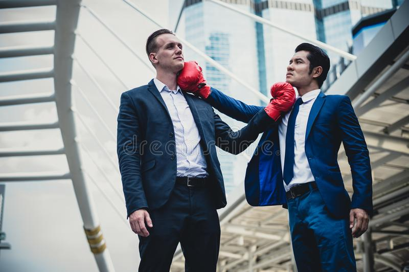 Caucasian affärsman och asiatisk affärsman med röda boxas handskar som slåss vid stansmaskin och uppercut Begrepp av affärskonkur royaltyfria bilder