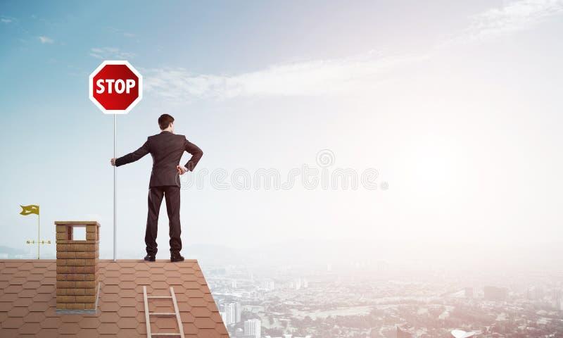 Caucasian affärsman på vägmärke för stopp för visning för tegelstenhustak Blandat massmedia royaltyfri foto