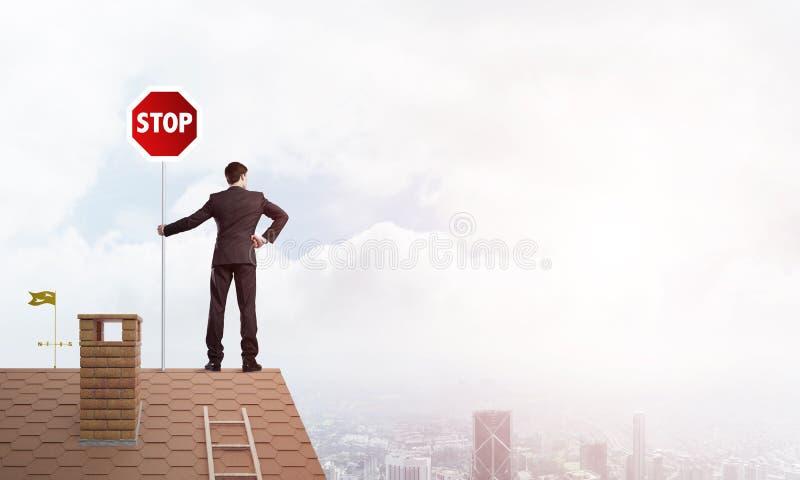 Caucasian affärsman på vägmärke för stopp för visning för tegelstenhustak Blandat massmedia royaltyfri bild