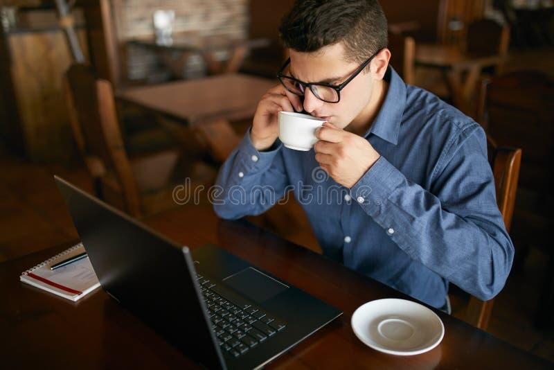 Caucasian affärsman som använder telefonen, medan arbeta på bärbar dator- och innehavkoppen kaffe i hand Multitaskingbegrepp uppt arkivbilder