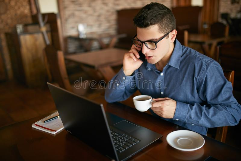 Caucasian affärsman som använder telefonen, medan arbeta på bärbar dator- och innehavkoppen kaffe i hand Multitaskingbegrepp uppt royaltyfri fotografi