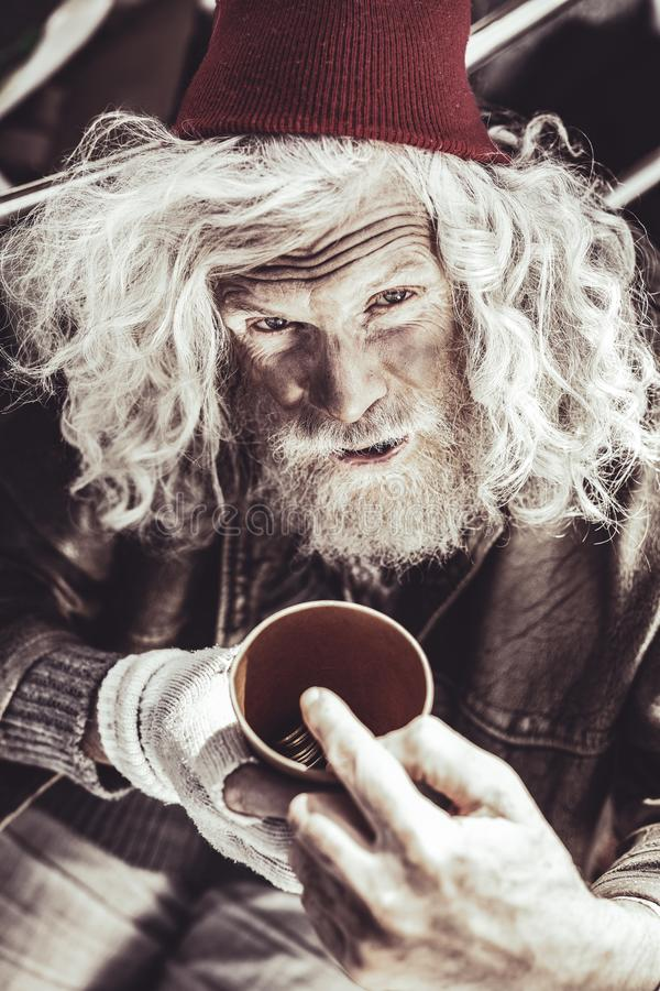 Caucasian almsman holding cup with money and showing his daily income. royalty free stock images