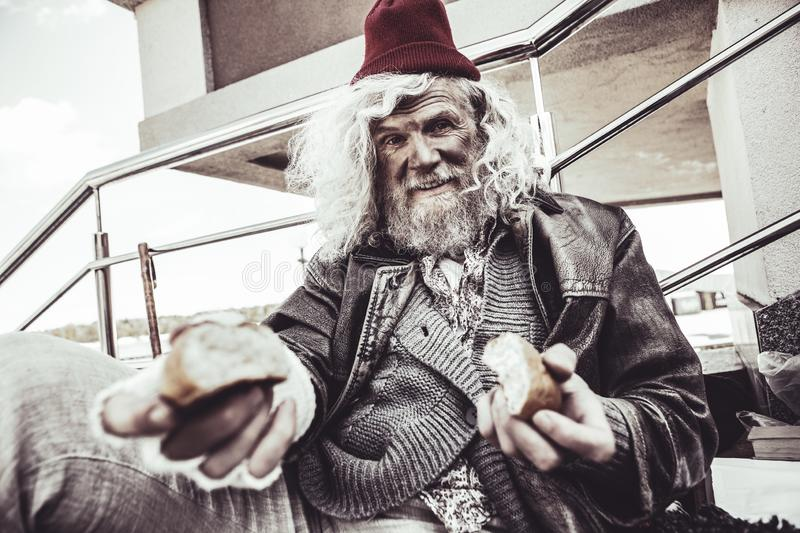 Caucasian almsman sitting and eating bun which he finding on the street. royalty free stock photos
