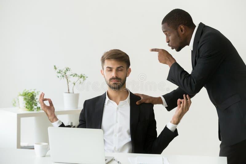 Caucasian anställd som mediterar på arbetsplatsen som ignorerar ilsket framstickande s royaltyfri foto
