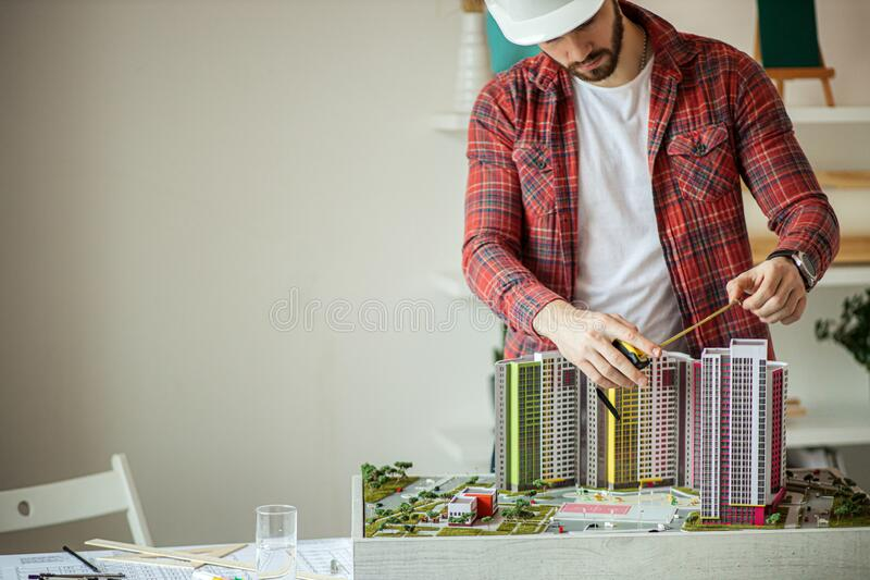 Architect man or designer working with building model in office. Caucasian architect man or designer working with small building model in office. design royalty free stock images