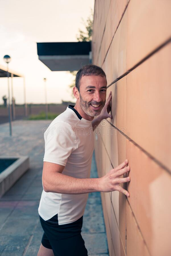 Caucasian athlete man in white t-shirt, hands resting on an orange brick wall, looking happily at the camera stock image