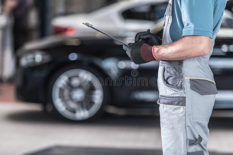 Vehicles Maintenance Work. Caucasian Auto Service Worker with Documentation. Vehicles Maintenance Work stock photos