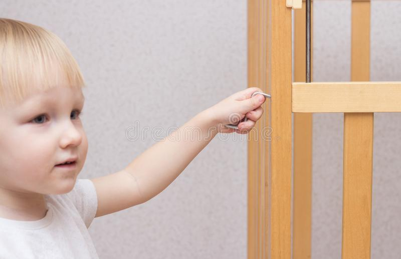 Caucasian baby assembles and repairs baby cot, close-up stock image
