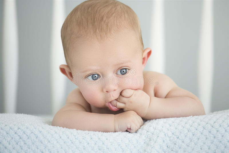 Caucasian baby boy. Cute baby caucasian boy lying on a soft blanket in a white crib stock images