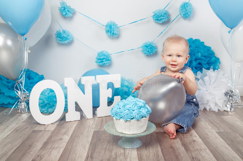 Caucasian baby boy in dark pants and blue bow tie celebrating his first birthday with letters one and balloons. Portrait of cute adorable blond Caucasian baby stock images