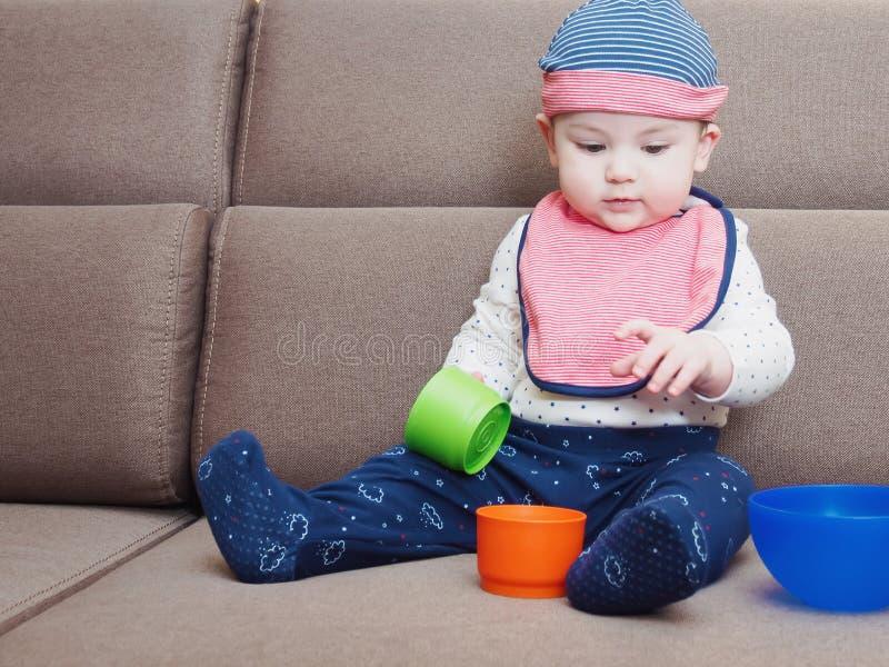 Caucasian baby boy weared bib sitting on sofa at home stock photography