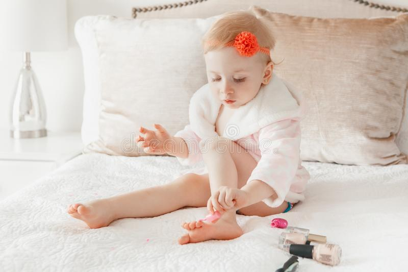 Caucasian baby girl painting nails sitting on bed at home. stock photo