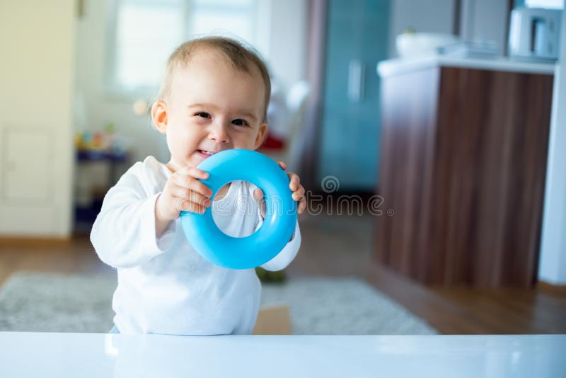 Caucasian baby girl standing next to table with blue torus in hands and laughing. Into camera. Copy space stock photos