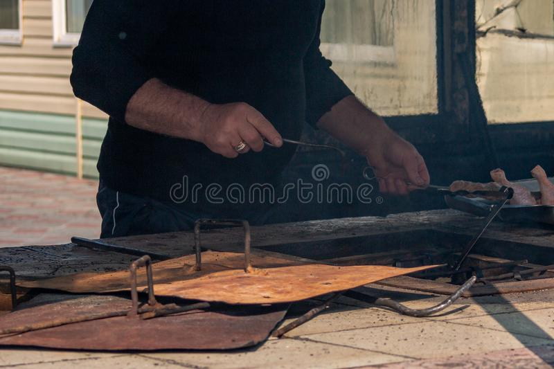 Caucasian barbecue chef preparing a tandoor for cooking chicken shashlik in an ordinary city location relaxing near the stock images