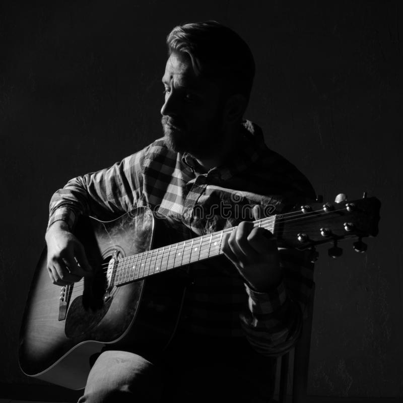 Caucasian bearded male musician playing guitar on stage, focus on hand. black and white.  stock photos