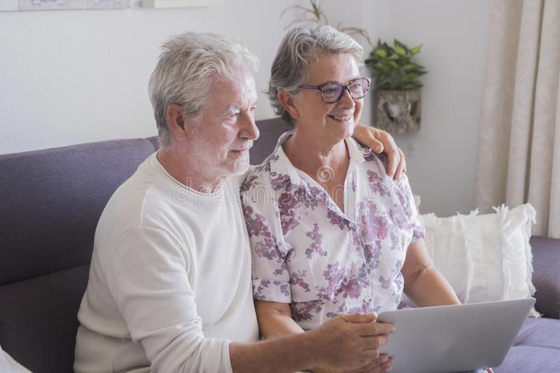 Caucasian beautiful couple of elderly senior adult at home using internet with a laptop together - internet for retired people in royalty free stock photography
