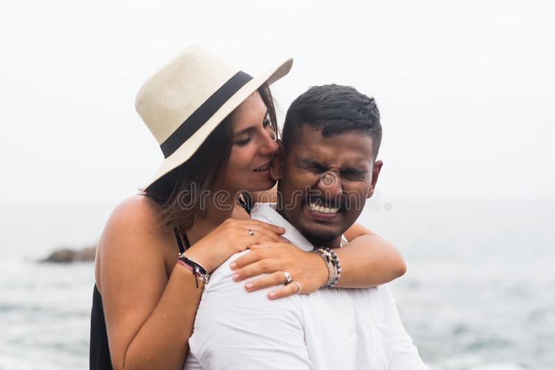 Caucasian beautiful woman hugs her husband and bites his ear a little. royalty free stock images
