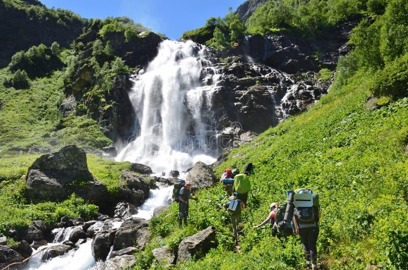 Caucasian biosfärreserv, Ryssland, Augusti, 02, 2017 Turister som fotvandrar till den övreImeretinsky vattenfallet på floden Imer arkivbilder