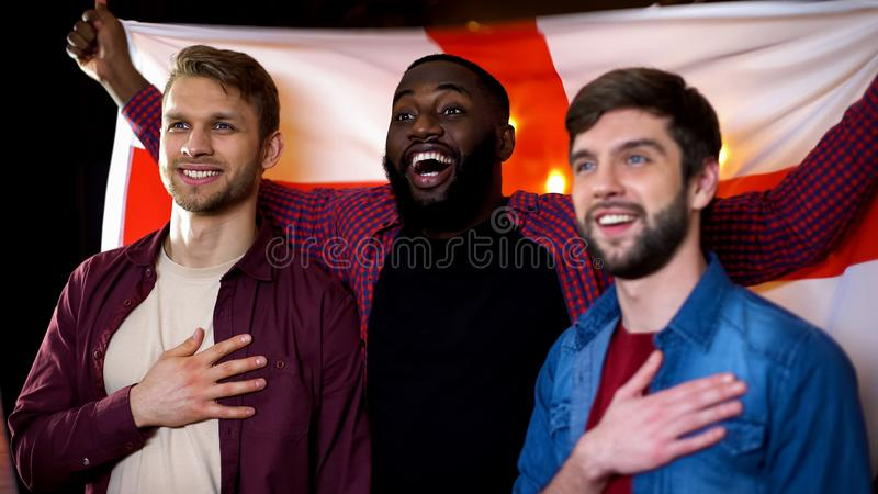 Caucasian and black male friends singing national anthem, waving english flag. Stock photo stock photos