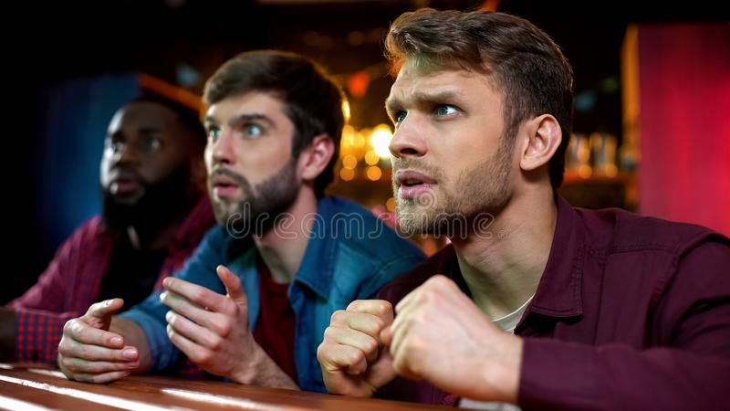 Caucasian and black male friends watching football game in bar, team losing royalty free stock image
