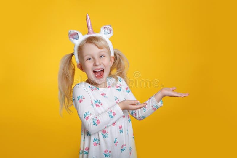 Caucasian blond flicka i för enhörninghuvudbindel för vit klänning bärande horn och öron arkivfoto