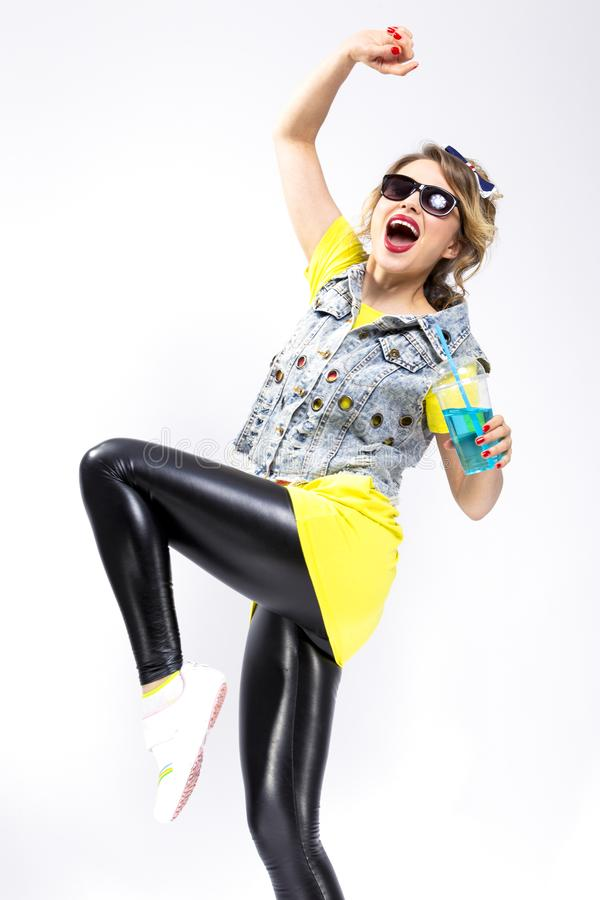 Caucasian Blond Girl Dancing With Cup of Blue Cocktail. Wearing Denim Vest and Sunglasses stock photo