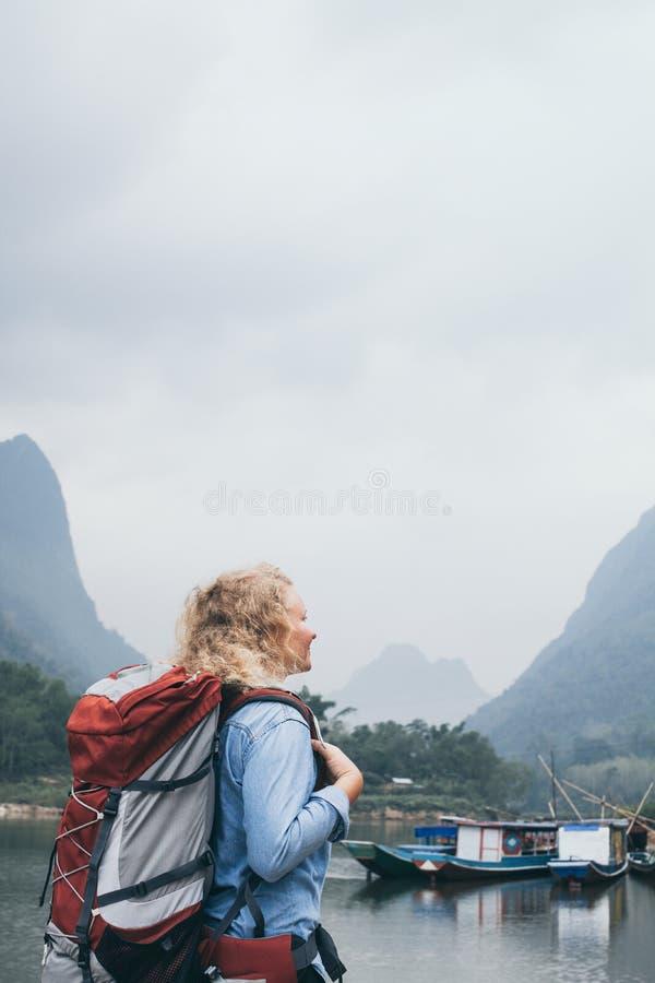 Caucasian blond kvinna med ryggsäckställningar på fartygpir i den Muang Ngoi byn, Laos royaltyfria foton
