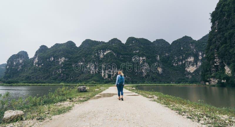 Caucasian blond kvinna som går in mot kalkstenberg i det Ninh Binh landskapet, Vietnam royaltyfri bild