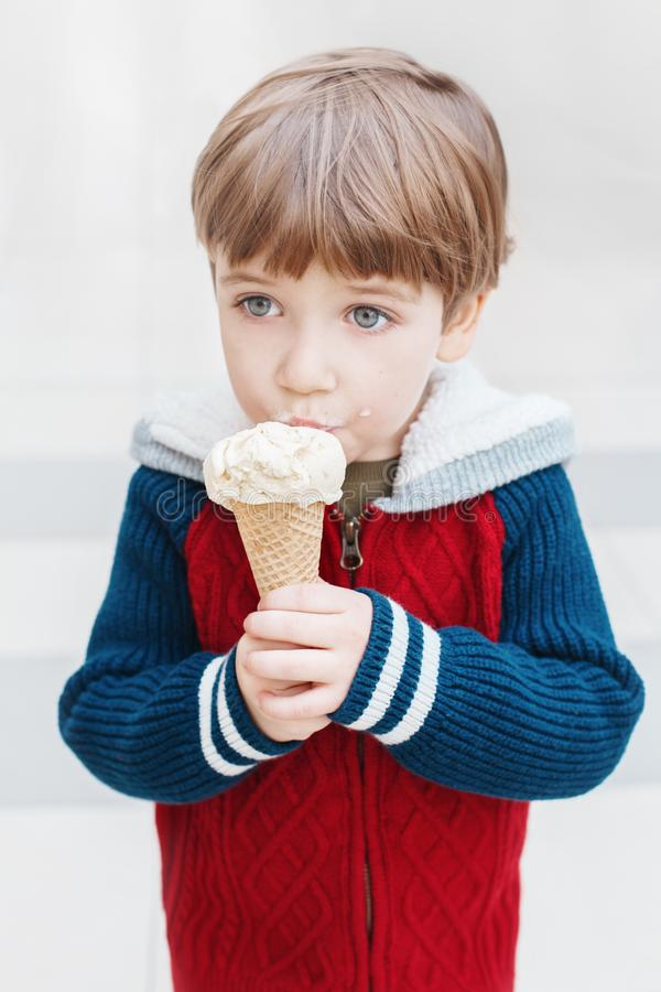 Caucasian blond preschool boy with green eyes in red sweater eating licking ice cream. Closeup portrait of cute white Caucasian blond preschool boy with green stock image