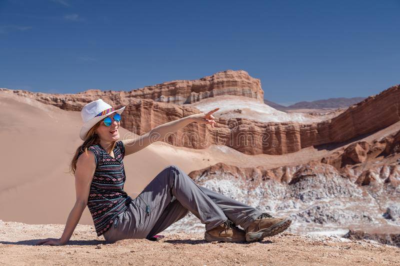 Casual woman enjoy solo trip and admire unique epic landscape of the Moon Valley, Chile. Caucasian blond woman enjoy solo trip and admire unique epic landscape stock image